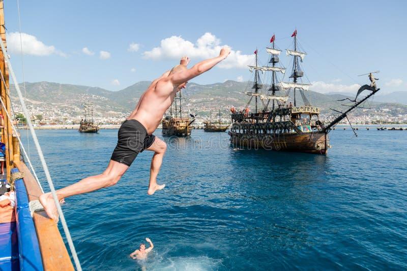 Alanya, Turquia - outubro, 09, 2016: O homem salta de um navio na água imagens de stock royalty free