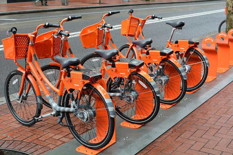 ` Alaranjado de quatro Aluguel-um-bicicletas do ` da cidade em Portland, Oregon fotos de stock