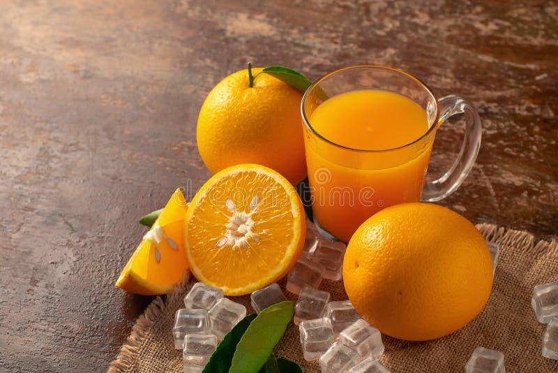 Alaranjado fresco e um vidro do suco de laranja em um backg de madeira da tabela fotografia de stock