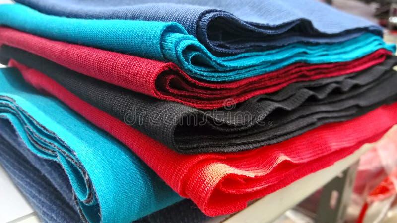 Alaranjado industrial, preto novos, vermelho e fundo azul do rolo Conceito: material, tela, fabricação, fábrica do vestuário, amo imagem de stock