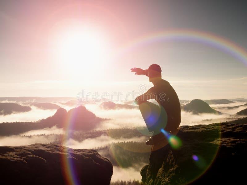 alargamento Defeito da lente, reflexões O homem no sportswear está sentando-se na borda do penhasco e está olhando-se ao vale ene fotos de stock