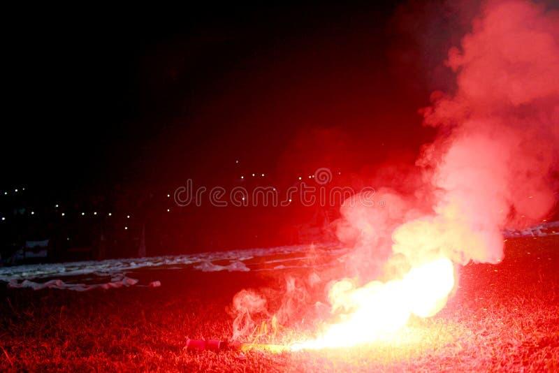 Alargamento vermelho ardente, chama, hooligan do futebol os fan de futebol iluminaram acima as luzes e as bombas de fumo no passo imagem de stock