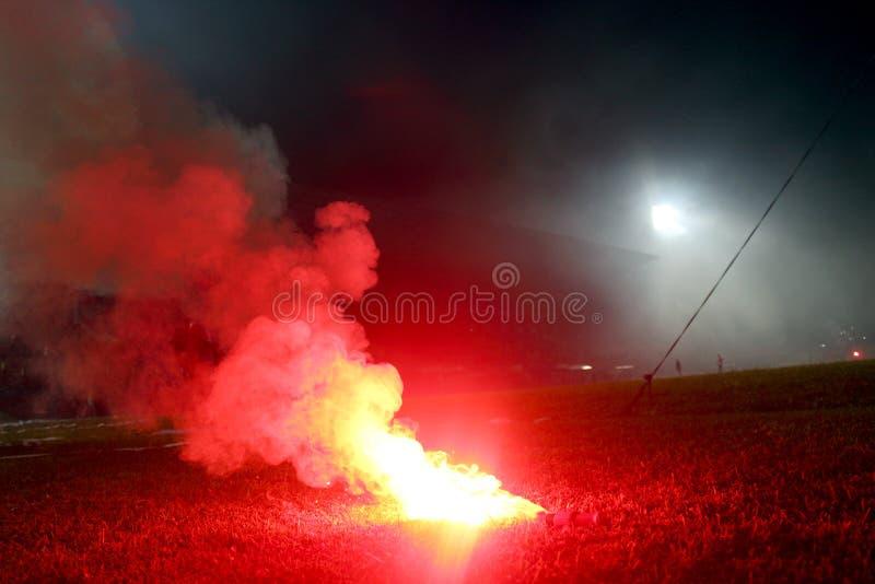 Alargamento vermelho ardente, chama, hooligan do futebol os fan de futebol iluminaram acima as luzes e as bombas de fumo no passo fotografia de stock