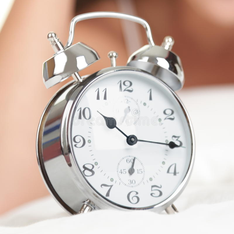 Alarm Clock. Woman in bed in background. Late for work stock photo