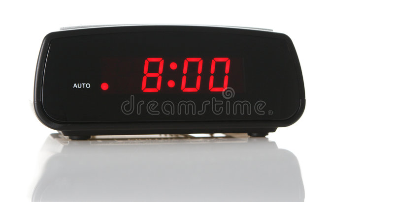 An Alarm Clock at 8am. A digital alarm clock showing 8:00am over white background with a natural reflection under it