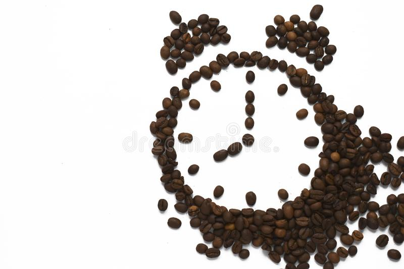 Alarm clock 8 AM arranged from roasted coffee beans. Time to awake drink espresso isolated on white background royalty free stock images