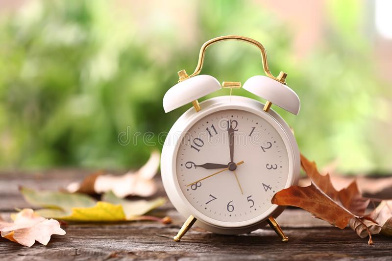 Alarm clock with autumn leaves on wooden table outdoors stock photos