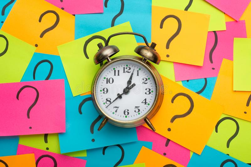Alarm clock on the background of the painted question on the sticker. copy space stock image