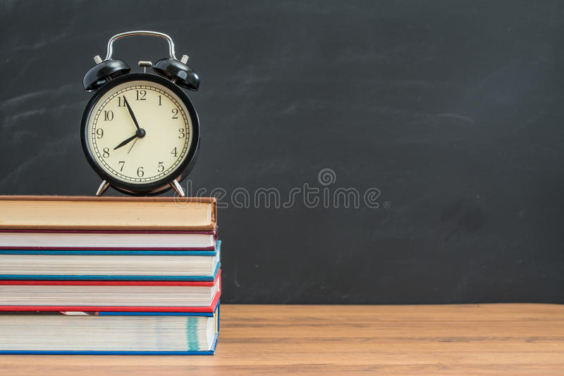 Alarm clock and book on student desk in front of blackboard stock image
