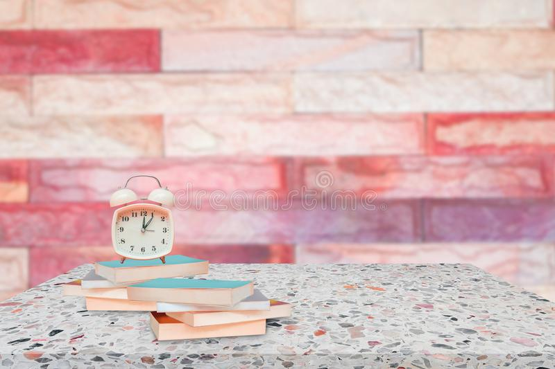 Alarm clock and books on stone shelf in library school concept with brick wall blur background. Copy space add text royalty free stock photography