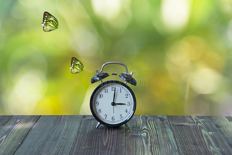 Alarm clock with butterfly on table royalty free stock images