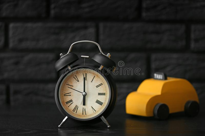 Alarm clock with car toy on dark table royalty free stock images