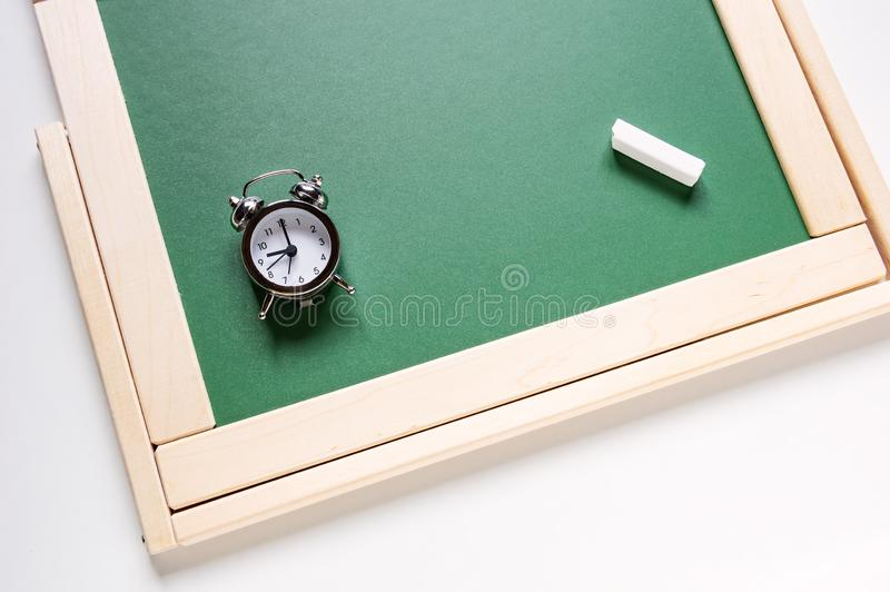Alarm clock and chalk for drawing on the background of green school blackboard stock images