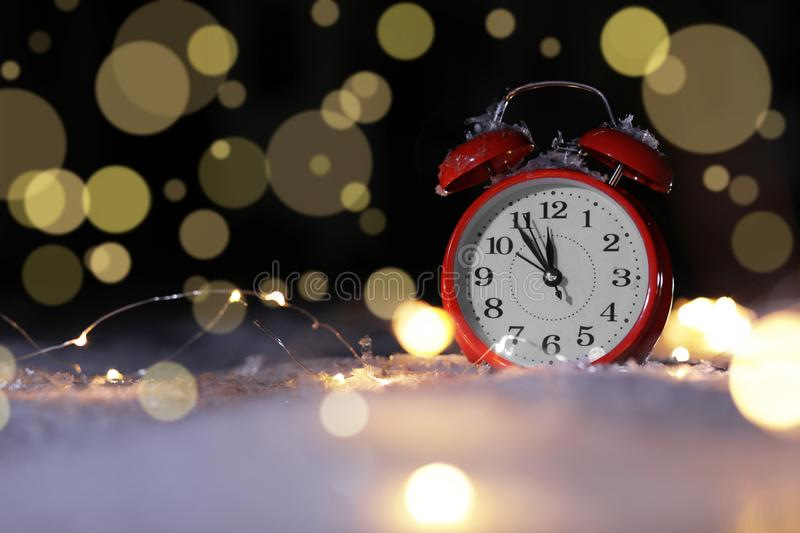 Alarm clock and Christmas lights on snow against blurred background, space for text. Winter night royalty free stock image