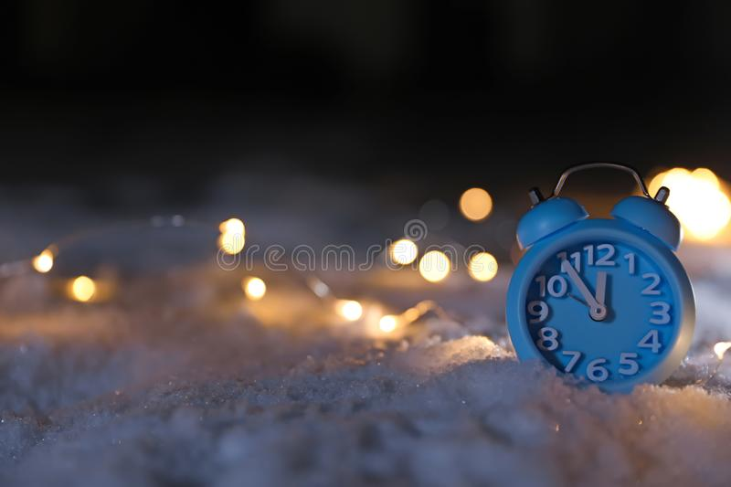 Alarm clock and Christmas lights on white snow outdoors, space for text. Midnight countdown stock photo