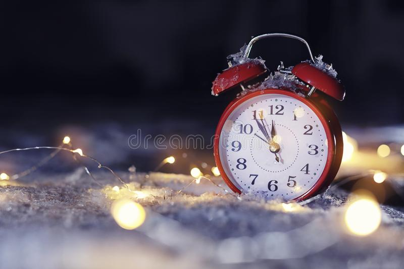Alarm clock and Christmas lights on white snow, space for text. Midnight countdown. Alarm clock and Christmas lights on white snow outdoors, space for text stock images