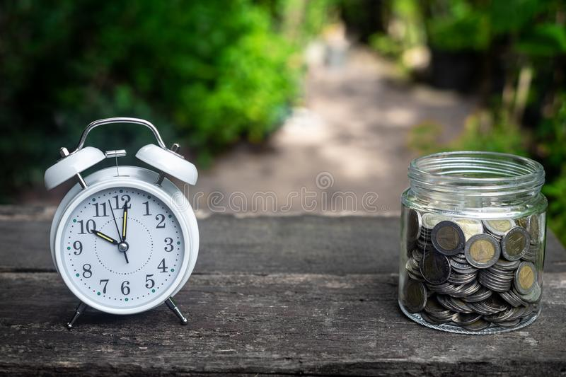 Alarm clock and coin in glass with garden background, finance and business concept. Copy space, vintage, retro, time, analog, financial, saving, growth, coins royalty free stock photos