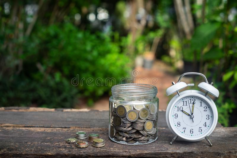Alarm clock and coin in glass with garden background, finance and business concept. Copy space, vintage, retro, time, analog, financial, saving, growth, coins stock photo