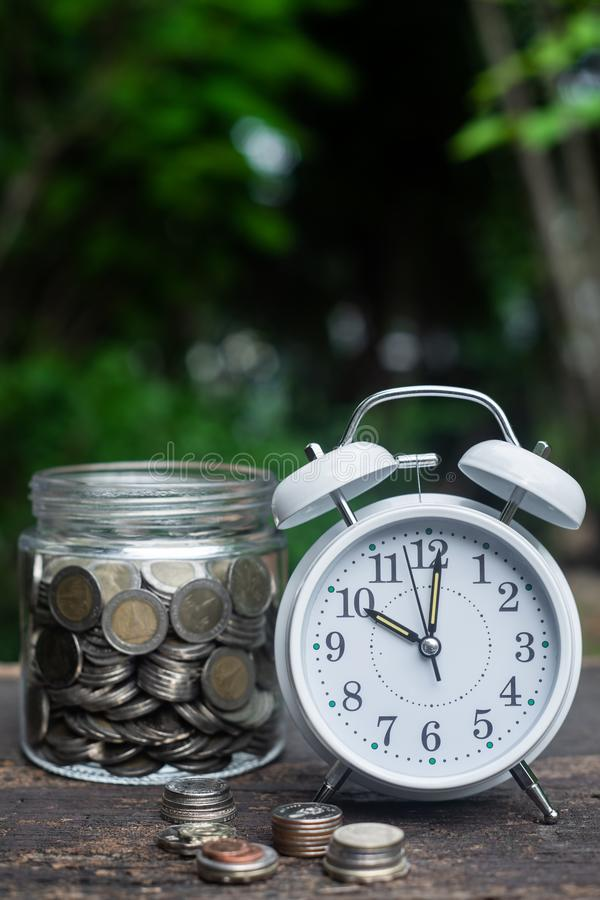 Alarm clock and coin in glass with garden background, finance and business concept. Copy space, vintage, retro, time, analog, financial, saving, growth, coins royalty free stock photo