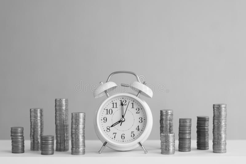 Alarm clock and coin piles arrange into growth chart on white background, finance and business concept. Copy space, vintage, retro, time, analog, financial royalty free stock images