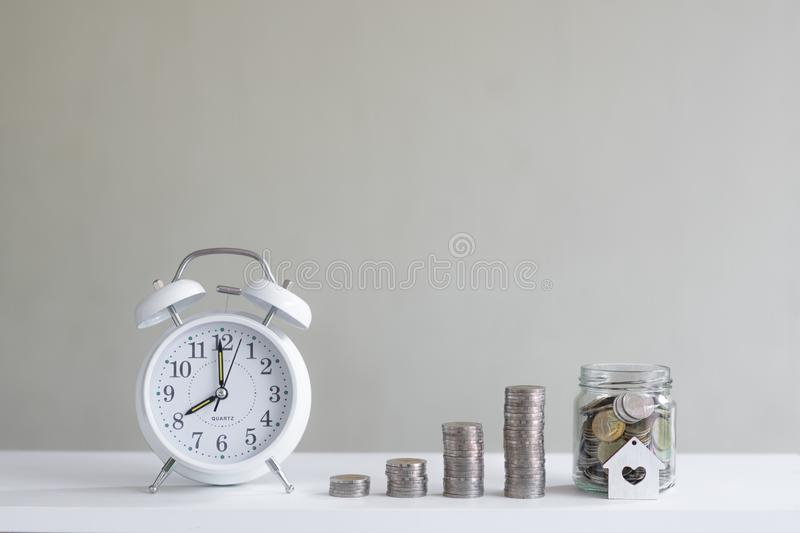 Alarm clock and coin piles arrange into growth chart on white background, finance and business concept. Copy space, vintage, retro, time, analog, financial royalty free stock photos
