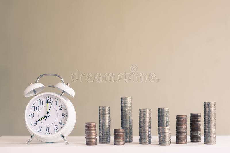Alarm clock and coin piles arrange into growth chart on white background, finance and business concept. Copy space, vintage, retro, time, analog, financial stock photos