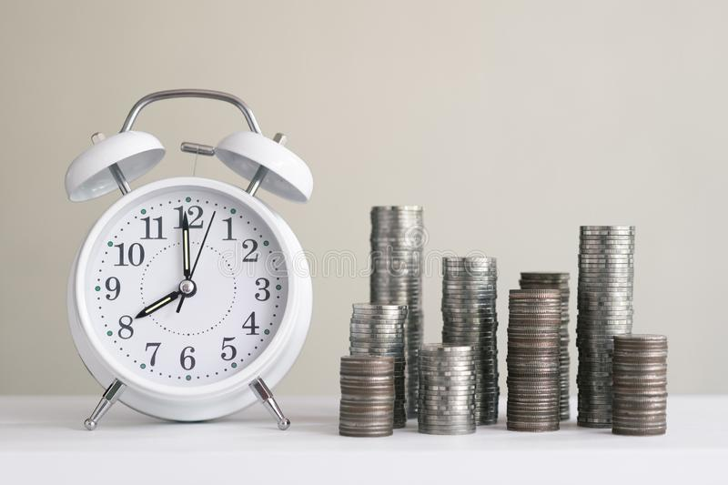 Alarm clock and coin piles arrange into growth chart on white background, finance and business concept. Copy space, vintage, retro, time, analog, financial royalty free stock photography