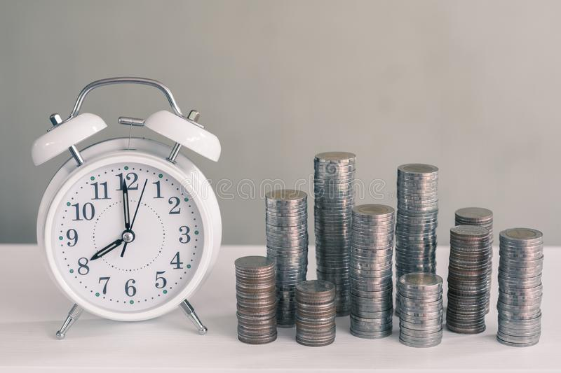 Alarm clock and coin piles arrange into growth chart on white background, finance and business concept. Copy space, vintage, retro, time, analog, financial stock photography