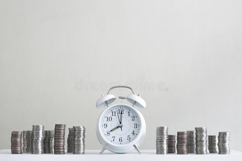 Alarm clock and coin piles arrange into growth chart on white background, finance and business concept. Copy space, vintage, retro, time, analog, financial stock image