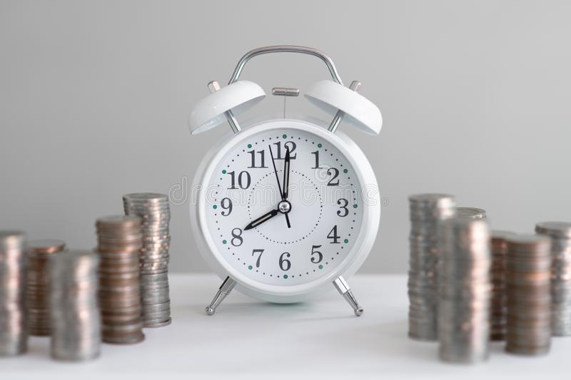 Alarm clock and coin piles arrange into growth chart on white background, finance and business concept. Copy space, vintage, retro, time, analog, financial royalty free stock photo