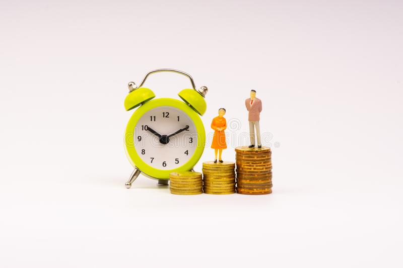 Alarm clock, coins and businessman miniature royalty free stock photo