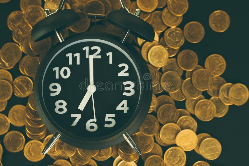 Alarm clock and coins stacks on working table, time for savings money concept, banking and business concept royalty free stock image
