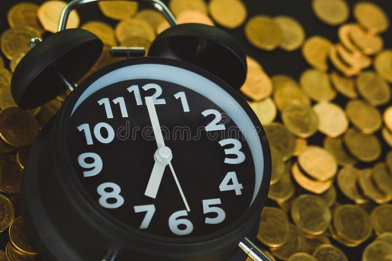 Alarm clock and coins stacks on working table, time for savings money concept, banking and business concept stock photos