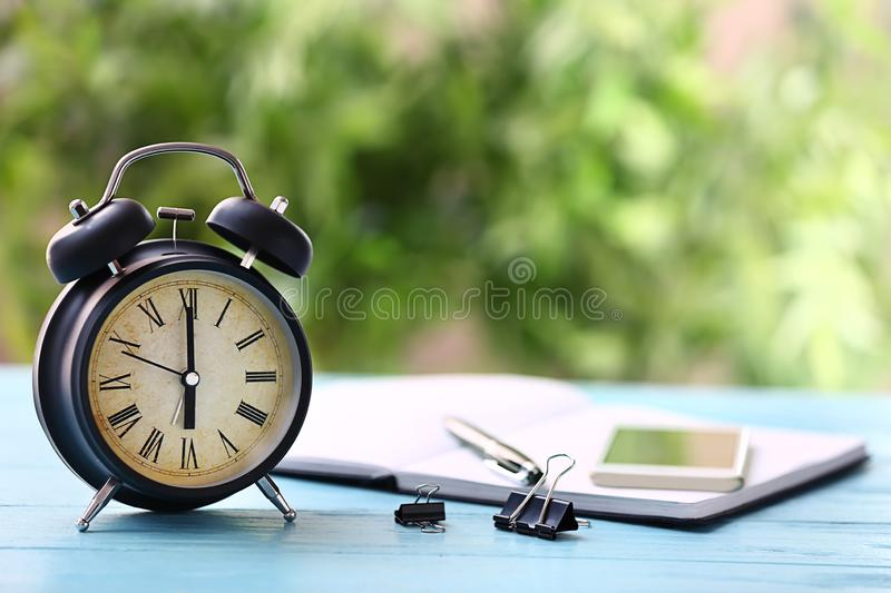 Alarm clock on color wooden table outdoors royalty free stock image