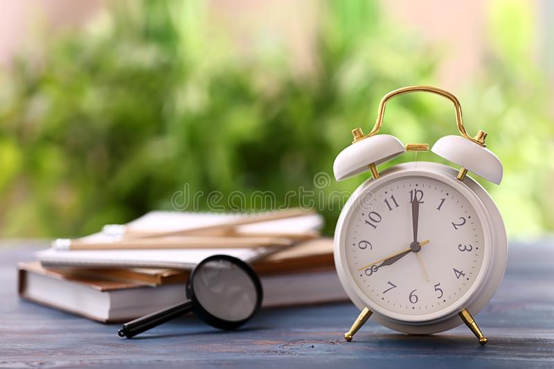 Alarm clock on color wooden table outdoors stock photos
