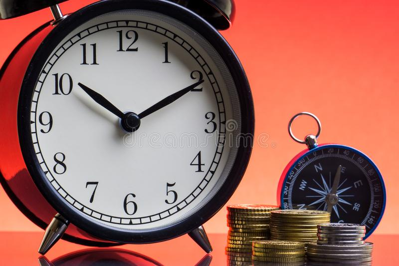 Alarm Clock, compass and coins on red background royalty free stock photos