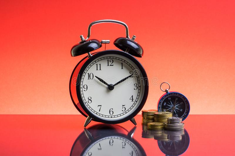 Alarm Clock, compass and coins on red background royalty free stock photo