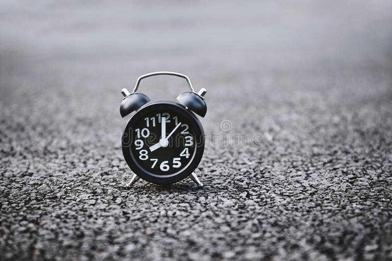 Alarm clock on the dark rough texture background with copy space. royalty free stock photo