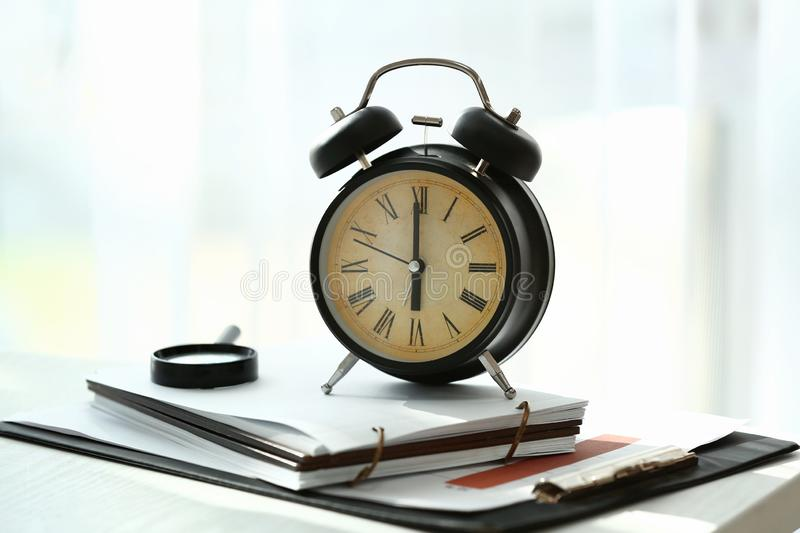 Alarm clock with documents on white table stock photos
