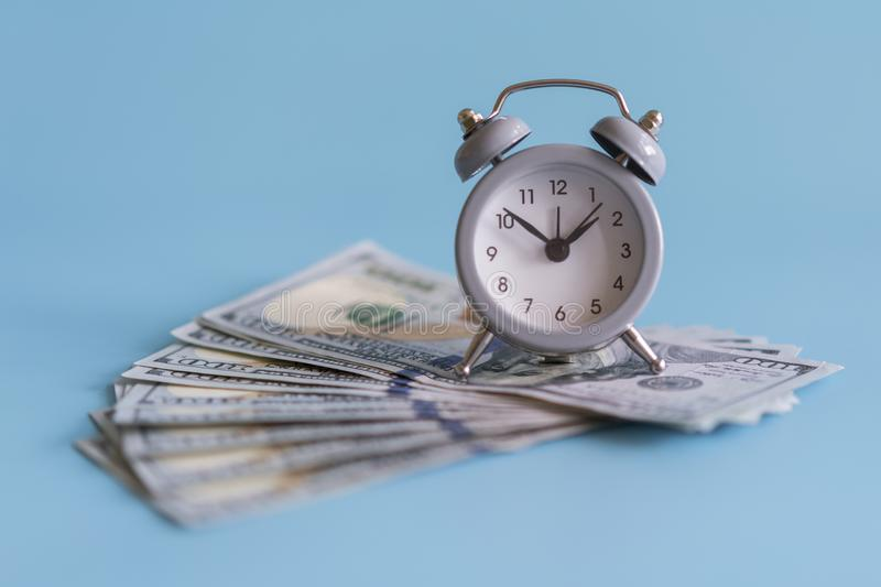 Alarm clock and dollars, close up. Time is money. Gray alarm clock on money banknotes Dollars, concept of business planning and fi stock photos