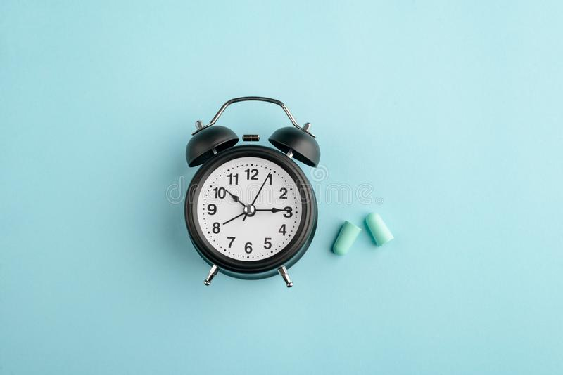 Alarm clock and earplugs. On blue background. Bedtime accessories, sleep schedule and sound block royalty free stock photo