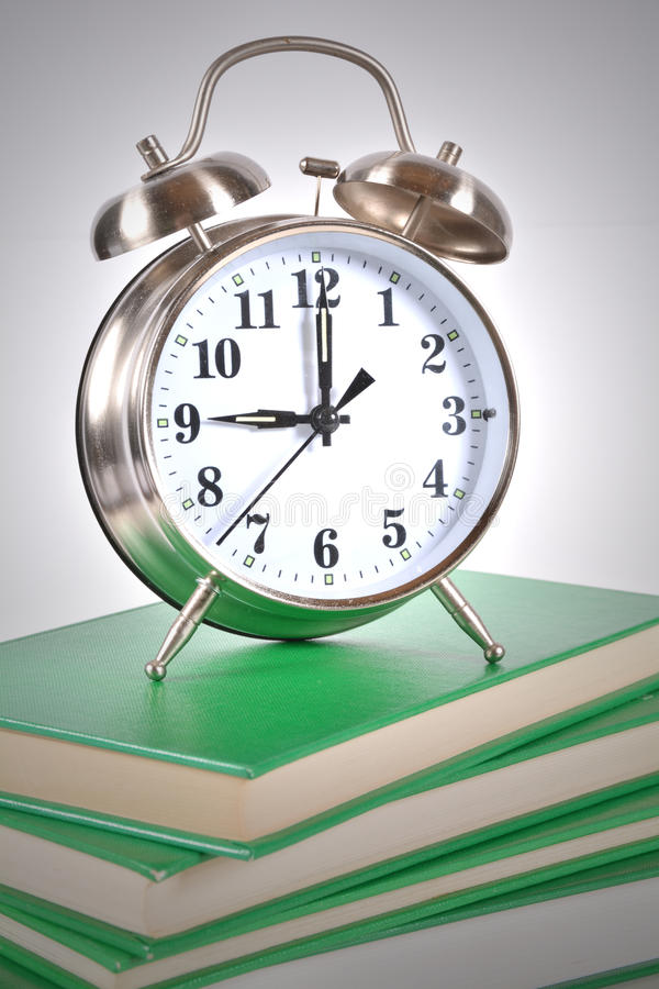 Alarm Clock Education. Alarm clock ontop of books - time to study concept royalty free stock photo
