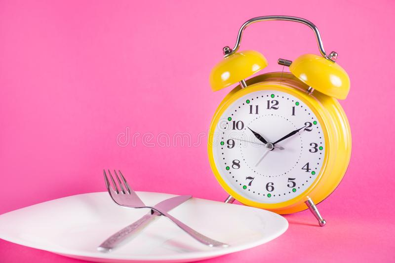 Alarm clock and empty plate with fork and knife. Chrono diet concept. Old alarm clock and empty plate with fork and knife isolated on pink background. Food and royalty free stock images