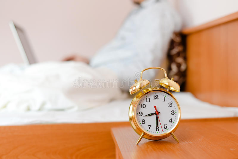Alarm clock on foreground and business man or woman sitting in white bed working on the laptop computer on background royalty free stock image