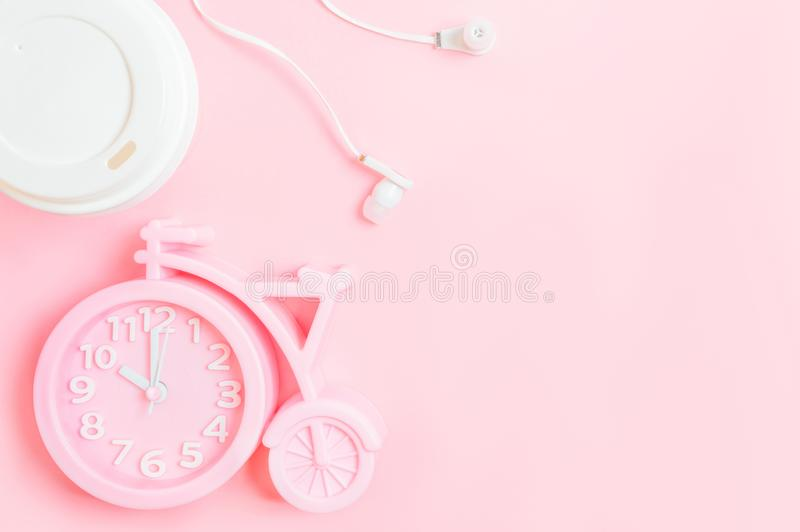 Alarm clock, a glass of coffee take-away and headphones on a pink background. Good morning or working space. Flat-lay, top view. Pink alarm clock in the shape of stock photography
