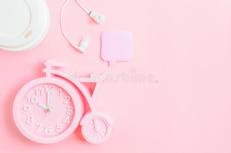 Alarm clock, a glass of coffee take-away, headphones and a recording stick on a pink background. Good morning or working space. Pink alarm clock in the shape of royalty free stock photography