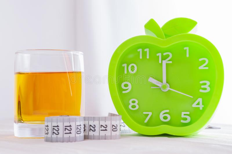 Alarm clock, a glass of juice and a measuring tape on a white wooden table. Good morning, healthy morning or diet concept. Green alarm clock in the shape of an stock photos