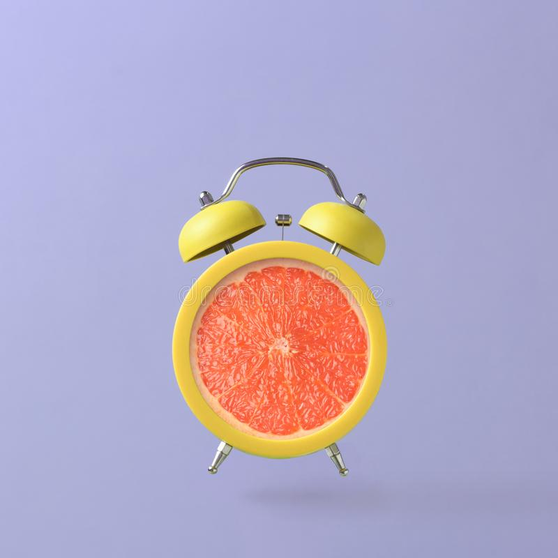Alarm clock with grapefruit. On colorful background. Summer time concept. Creative minimal still life royalty free stock photos