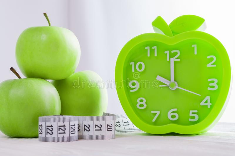 Alarm clock, green apples and a measuring tape on white wooden table. Good morning, healthy morning or diet concept. Green alarm clock in the shape of an apple stock images