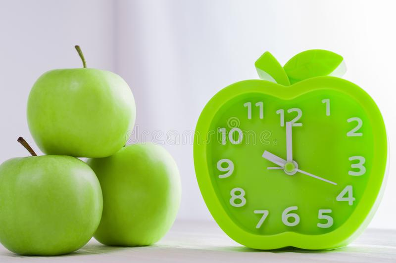 Alarm clock and green apples on white wooden table. Good morning, healthy morning or diet concept. Green alarm clock in the shape of an apple and fresh green royalty free stock photo